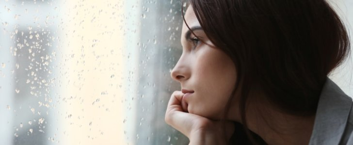 Depressed woman stares out of the window on a rainy day