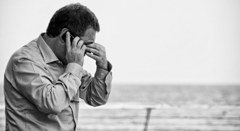 Man on cellphone struggles with stress
